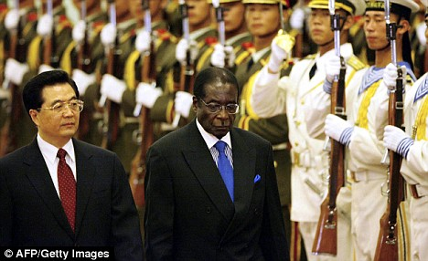 Chinese President Hu Jintao accompanies Zimbabwe President Robert Mugabe to a ceremony in the Great Hall of the People in Beijing