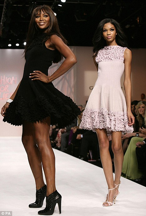 Naomi Campbell and a model strut their stuff on the catwalk