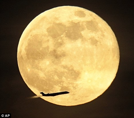 A jet takes off from Dallas-Fort Worth International Airport as the enlarged full moon rises in the background