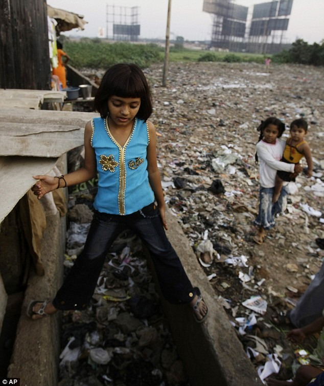 Rubina Ali Qureshi, 9, left, straddles a blocked drain next to an open area strewn with garbage near her home in a slum in Bandra, suburban Mumba
