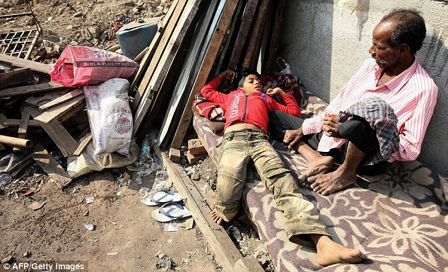 Three days ago: Mohammed Azharuddin relaxes on a cot along with his father outside their shanty in the Behrampada slums of Mumbai on February 19