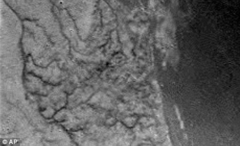This is one of the first raw images returned by the ESA Huygens probe during its successful descent. It apparently shows short, stubby drainage channels leading to a shoreline