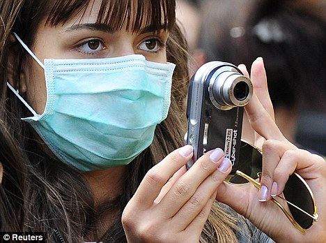 Facemask nation: A girl takes a photograph in Whitehall in London