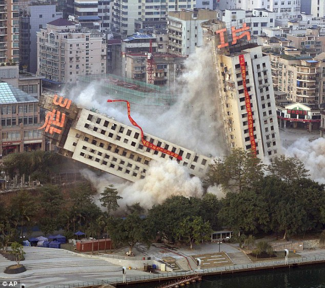 Not quite as planned: Another view catches the moment half the building goes down while the other half remains leaning