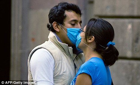 A couple in Mexico attempt to kiss while wearing the masks