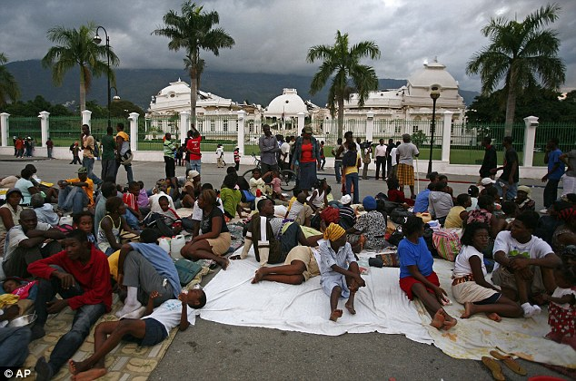 Survivors gather outside Haiti's National Palace which was badly damaged in the earthquake