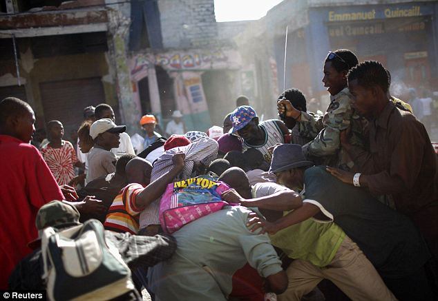 People fight over looted goods from a destroyed store after the earthquake