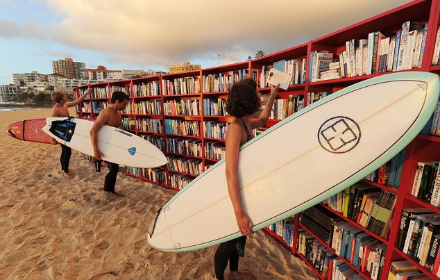 Surfers browse a bookcase on Bondi beach