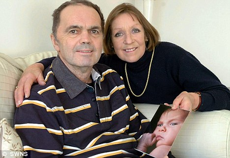 Farmer David Russell with wife Helen and a photograph of new granddaughter Edie. Doctors thought David would wake from his coma with severe brain damage