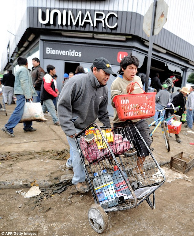 Haste: Looters rush away from a supermarket in Pueco, 10kms from Concepcion