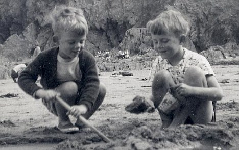Brotherly love: Peter, left, and Christopher, right, play in the sand during a holiday in Devon in the fifties