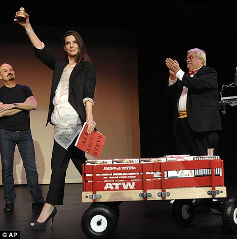 Good sport: Sandra Bullock accepts her Razzie award for worst actress in a feature film - bringing with her a cart full of DVDs and the script for All About Steve