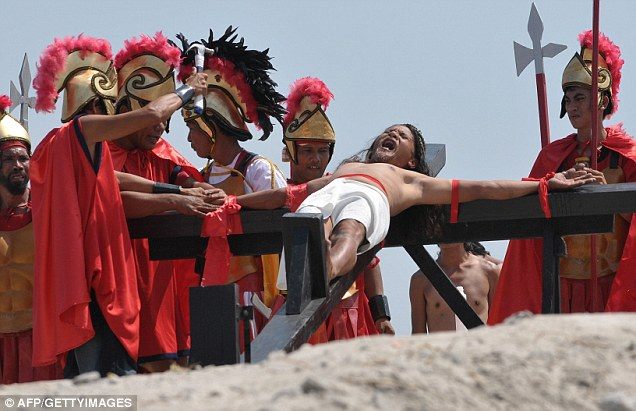 Painfully devoted: Ruben Enaje, a 49-year-old sign painter, was nailed to a cross for the 24th time as his way of thanking God for his survival after falling from a building. The bizarre practice is an annual Filipino ritual to mark Good Friday.