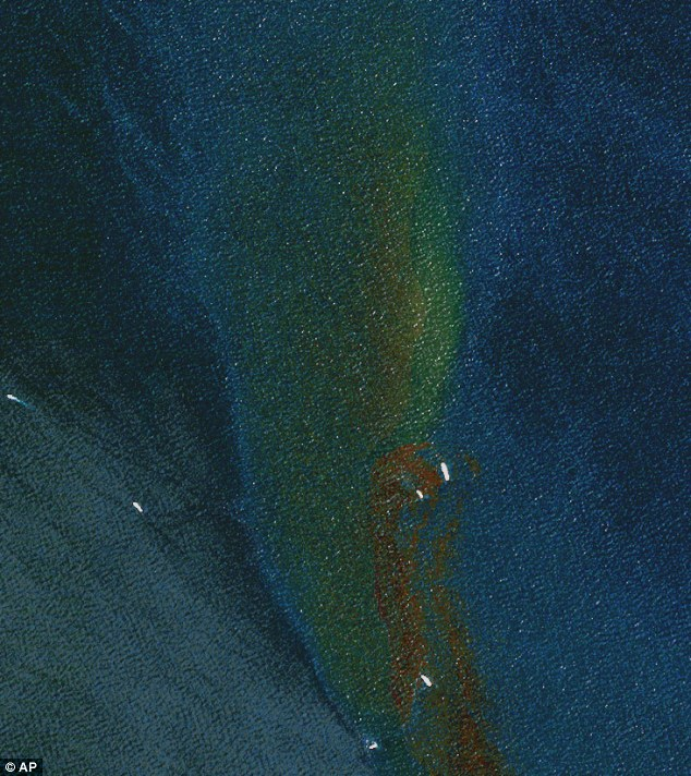 Lethal: A satellite image taken on Monday by DigitalGlobe shows vessels working to clean up the oil slick - (DigitalGlobe - AP - Mail Online UK)