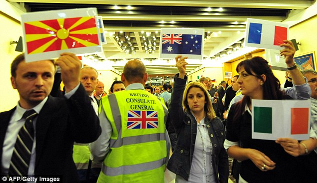Officials from European consulates hold up placards with national flag as they wait for compatriots to arrive at Istanbul airport
