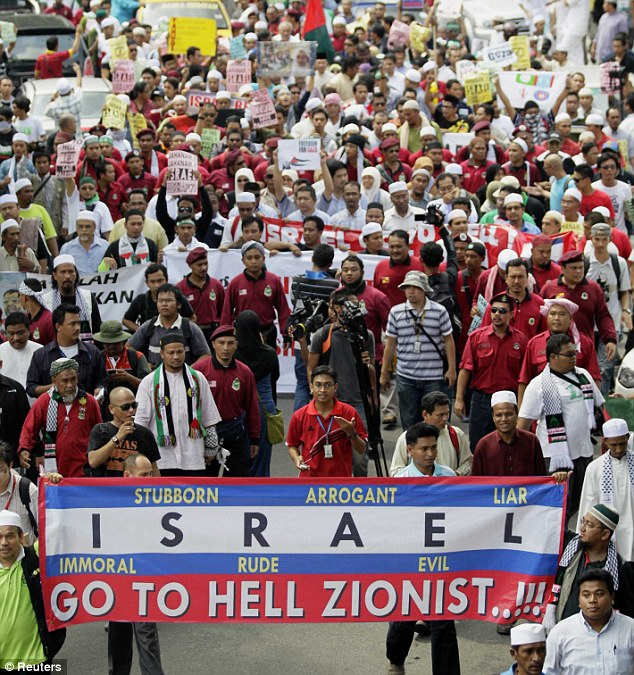 World outrage: Demonstrators display an anti-Israel banner as they march to the U.S. embassy in Kuala Lumpur today, to protest against Israel's storming of a Gaza-bound aid flotilla on Monday
