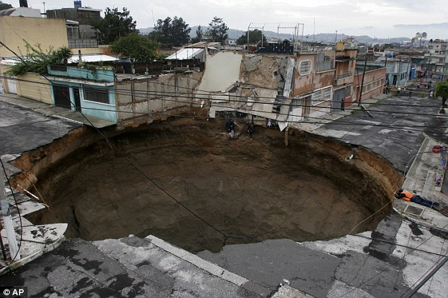 Devastation: A factory and intersection were swallowed up by a 66ft-wide sinkhole that opened up after storms in Guatemala