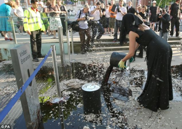 Protest: A woman pours oil and feathers outside the entrance to  the Tate Britain in central London, which is hosting the Tate Britain  summer