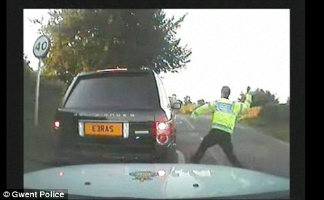 Caught on camera: Two police officers were suspended after a pensioner was left terrified by police who smashed in his car windows after catching him driving without a seatbelt. The episode was captured on a police video