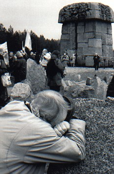 In memoriam An elderly Jewish Canadian weeps as he leans against a  symbolic tombstone near the Treblinka monument