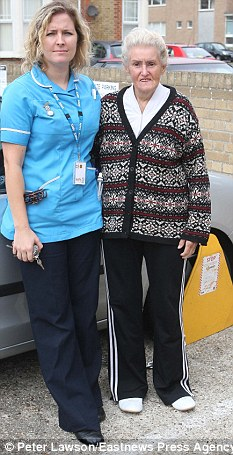Battle: Mrs Bannock pictured with her patient Iris Griffin in  front of her clamped car