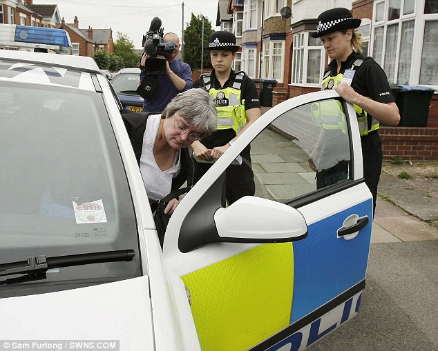 Mary Bale is escorted by officers from a house in Coventry into a police car today