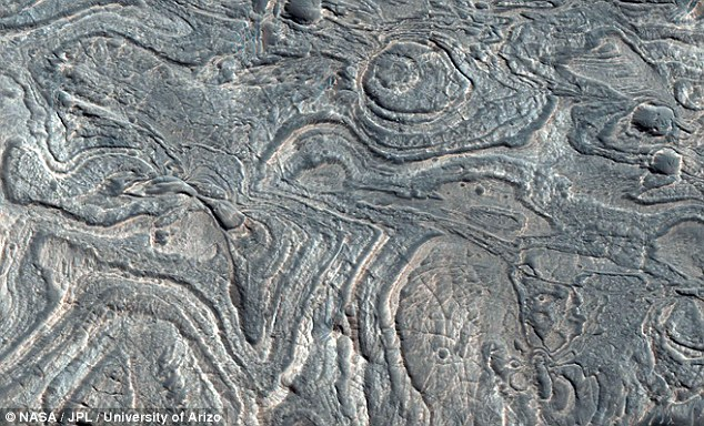 Close-up: Part of the Melas Chasma, a vast canyon on Mars, exposes  layered deposits that may be sediments from an old lake or they could  be windblown sediment deposits and volcanic ash