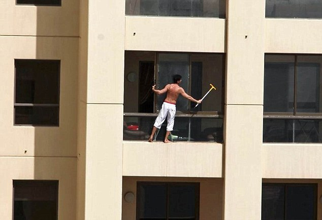 Stretching a point: The window cleaner uses a long-handled brush to reach the corners