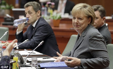 Entente cordiale: Angela Merkel pulls a face during an EU summit in Brussels. She is said to have advised President Sarkozy not to unveil the aircraft