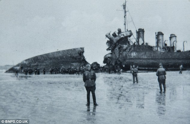 German troops examine a beached British ship with a giant hole in it