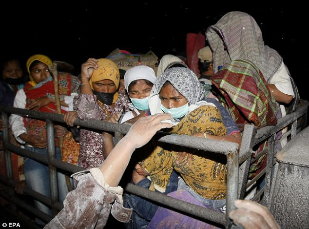Huddled together in fear: Refugees leave their camp to be evacuated to a safer place in Magelang as authorities extended the danger zone to 12 miles