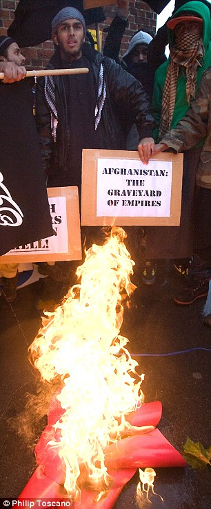 Inflaming tensions: The Muslim protesters set fire to a poppy near Hyde Park today