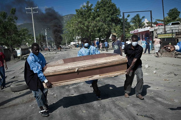 Grim task: Workers w ear protective masks as they carry the coffin of a cholera victim to be buried