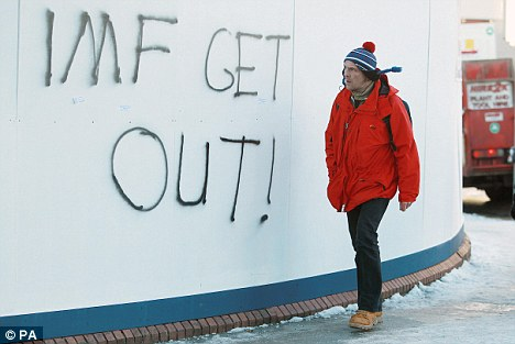 A man walks past fresh graffiti in Dublin against the IMF Bailout as Ireland braces itself for today's budget