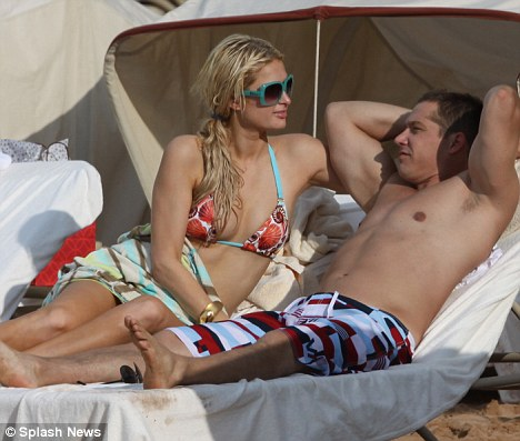 Getting cosy: The couple looked relaxed as they sat together on a sun lounger on the beach