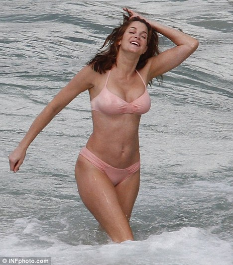 Heady times: The model plunged into the surf in a flesh coloured bikini