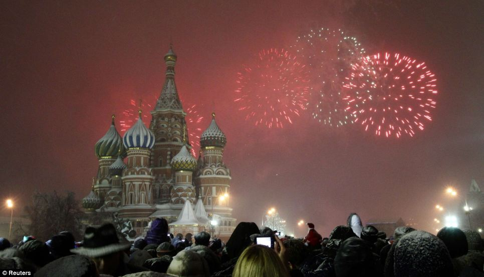 Red sky at night: Crowds have gathered in Moscow's Red Square as Russia welcomes in the New Year