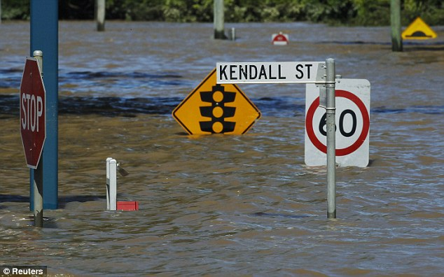 Worst hit: Street signs are submerged in flood waters in Bundaberg, Queensland
