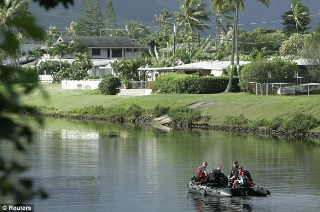 Security: A Coast Guard patrol dingy rides up the canal near the house in Kailua where President Obama is staying