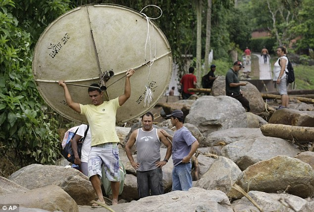 Salvage: A man carries a satellite dish recovered from the debris after a landslide in Campo Grande neighborhood, in Teresopolis
