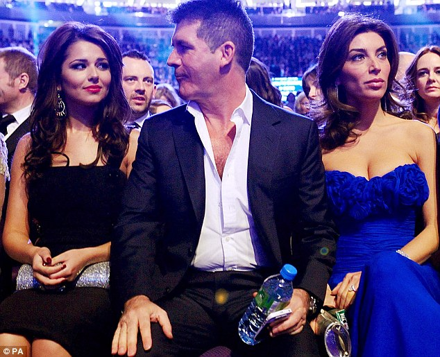 Alright, pet: Cheryl Cole and Simon Cowell lock eyes as the X Factor boss's fiancée Mezhgan Hussainy watches the stage at the 2011 National Television Awards at London's O2 Arena last night