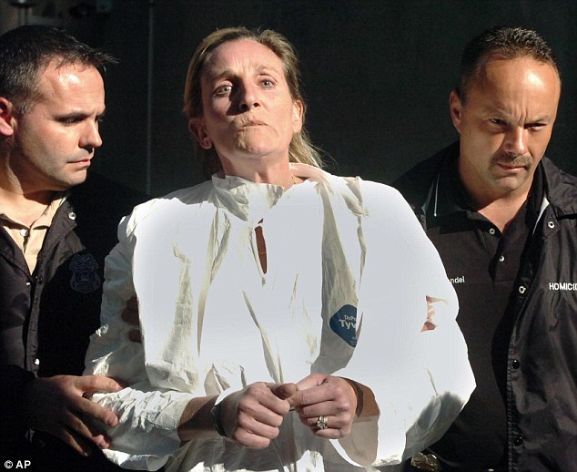Held: Julie Schenecker, 50, is led away by police officers after confessing to shooting her teenage children dead