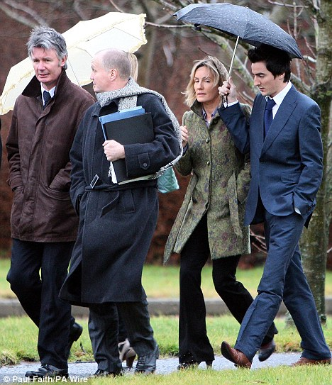 Court date: Stewart arrives at Coleraine Court on Monday with her husband David (far left) and her son Andrew (right)