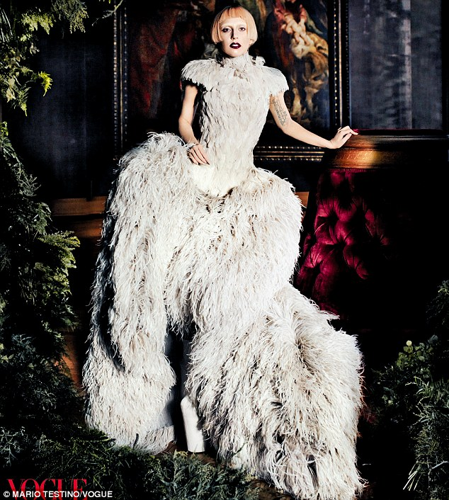 Striking: Lady Gaga sports a short pink wig and white feathered dress as she poses for this month's issue of Vogue magazine