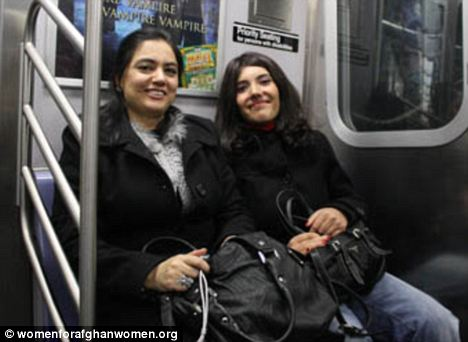 Bibi Aisha, now 20, is all smiles as she rides the subway with a friend. The young lady managed to flee Aghanistan after her nose and ears were hacked off by her husband
