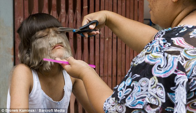 Supatra gets her hair cut by her mother in Bangkok, Thailand
