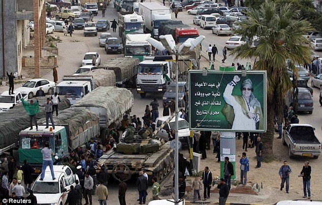A convoy of 18 trucks loaded with humanitarian aid bound for Benghazi travels past a Libyan army tank and a mural adulating Gaddafi in the Tripoli suburb of Gaser Ben Ghisher today