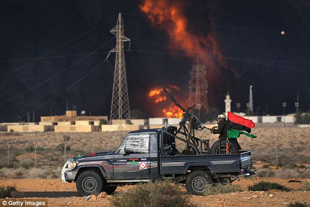 Black clouds: Libyan rebels attack government troops as a natural gas facility burns on the frontline near Ras Lanuf today
