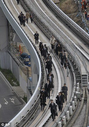 Yurikamome train passengers walk on the elevated track towards Shiodome Station in Tokyo's Shiodome district