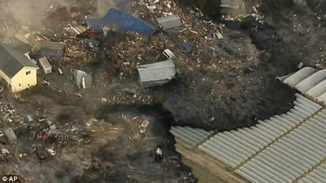 Creeping dread: In this image from Japan's NHK TV video footage, houses are washed away by tsunami in Sendai as the waves power ashore